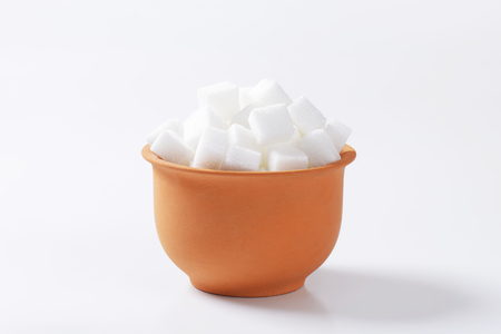 sugar cubes: White sugar cubes in terracotta dish