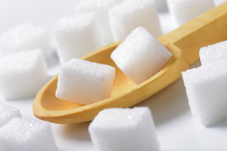 sugar cubes: White sugar cubes and small wooden spoon