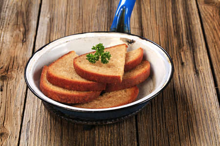 browned: Slices of fried bread in a pan