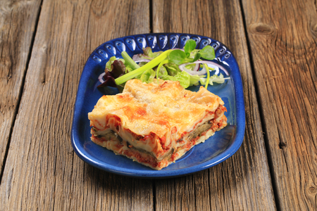 a portion: Portion of lasagna garnished with salad greens Stock Photo