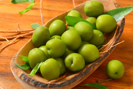 hand carved: Fresh green olives in natural wood bowl Stock Photo