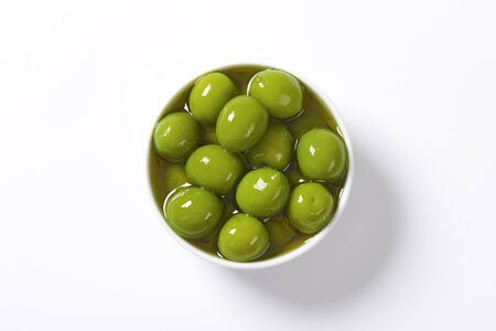 Bowl of green olives in oil