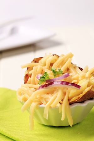 edam: Baked potato sprinkled with grated edam cheese Stock Photo
