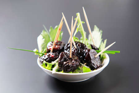prunes: Bowl of prunes on sticks and salad greens