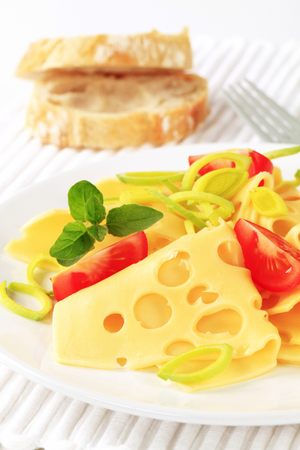 swiss cheese: Slices of Swiss cheese sprinkled with chopped leek