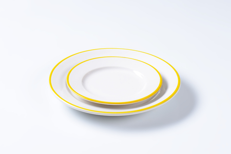 side plate: Dinner plate and side plate with yellow colored edges Stock Photo