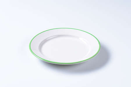 rimmed: Rimmed dinner plate with green colored edge Stock Photo