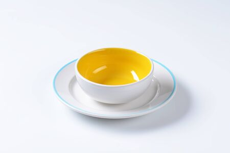 White and yellow coupe bowl and blue edged dinner plate