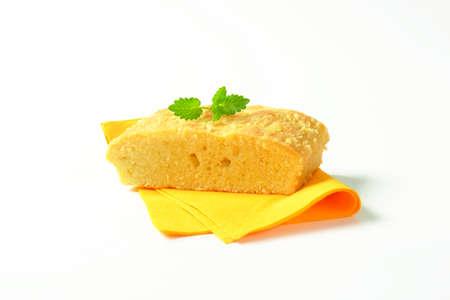 servilleta de papel: Rebanada de pastel de Madeira almendra en la servilleta de color amarillo Foto de archivo