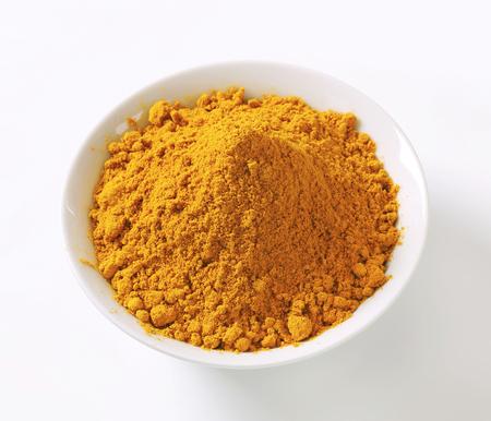 fenugreek: Heap of curry powder in a bowl Stock Photo