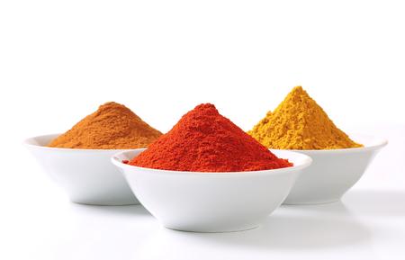 pimenton: Cuencos de polvo de curry, pimentón y canela molida Foto de archivo