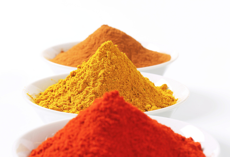 curry powder: Bowls of curry powder, paprika and ground cinnamon