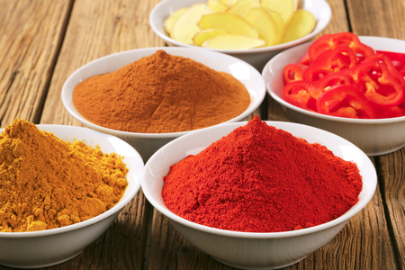 curry powder: Bowls of curry powder, paprika,  ground cinnamon, sliced ginger root and red pepper
