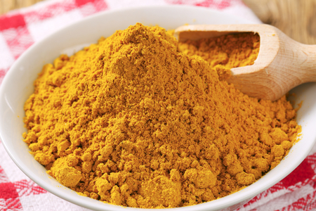 curry powder: Heap of curry powder in a bowl Stock Photo