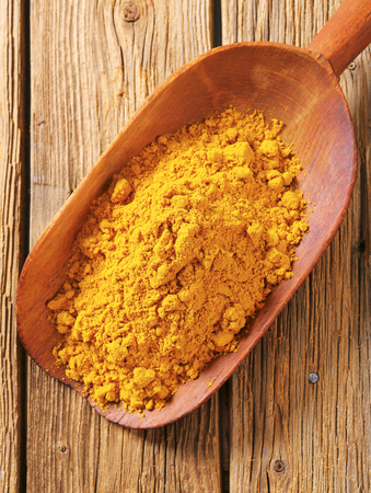 curry powder: Heap of curry powder on a wooden scoop