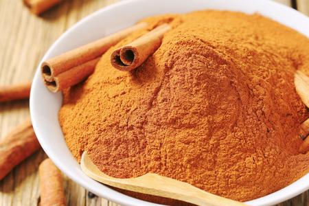 cinnamon sticks: Bowl of ground cinnamon and cinnamon sticks