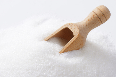 wooden scoop: Heap of white sugar and wooden scoop
