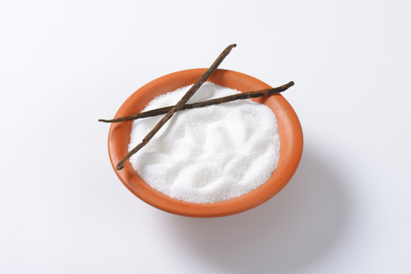 granulated: Bowl of white granulated sugar and two dried vanilla beans