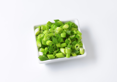 chopped: Chopped spring onions in square bowl