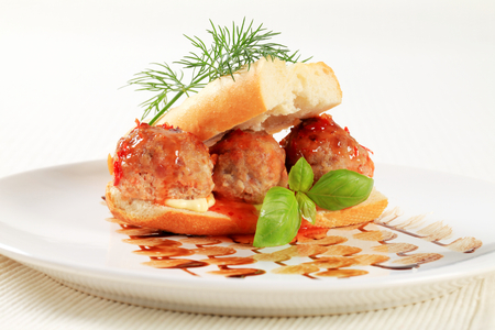 French loaf stuffed with meatballs and topped with red sauce photo