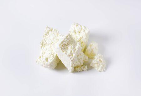 queso: Pedazos de queso de cuajada en el fondo blanco Foto de archivo