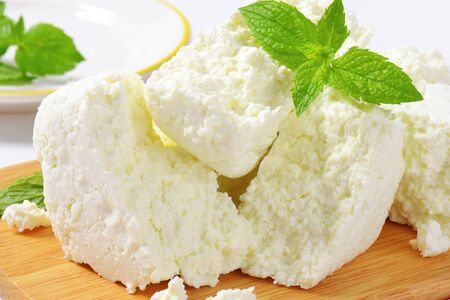 crumbly: Crumbly white cheese on cutting board Stock Photo