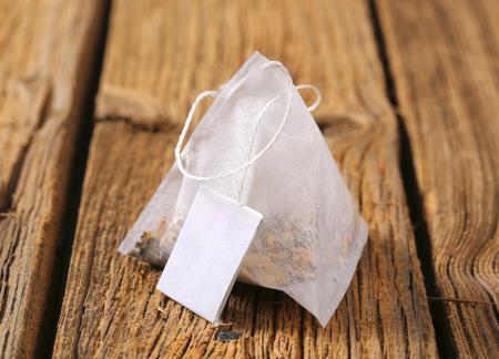 tea bag: Pyramid-shaped tea bag on wood Stock Photo