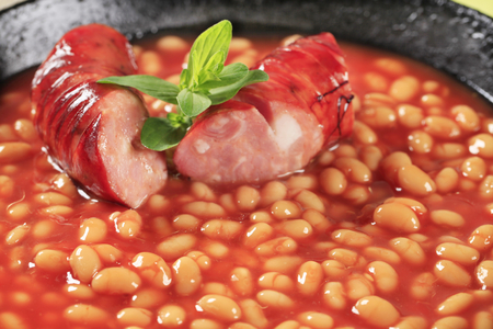 lima beans white beans: Baked beans with spicy sausage in a frying pan Stock Photo