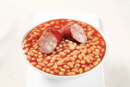 lima beans white beans: Baked beans and sausage in a white bowl