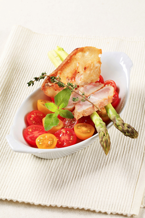 Healthy dish of cherry tomatoes, asparagus spears and slices of meat photo