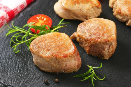 seared: Pan seared pork medallions on black slate Stock Photo