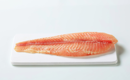 Raw skinless fish fillet on cutting board photo