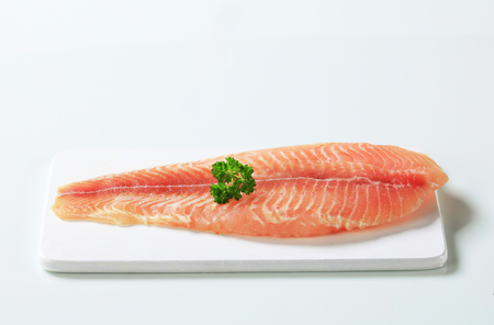 boned: Raw skinless fish fillet on cutting board