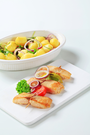 casserole dish: Fish skewer and potatoes in casserole dish