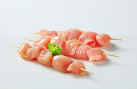 Pieces of raw chicken meat on skewers