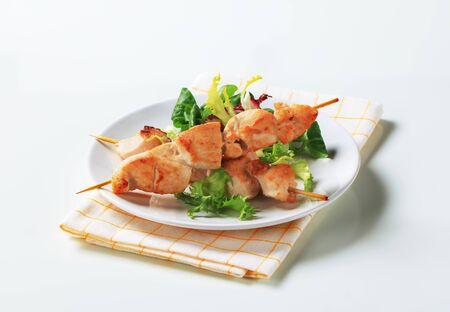 salad greens: Chicken skewers and mixed salad greens Stock Photo