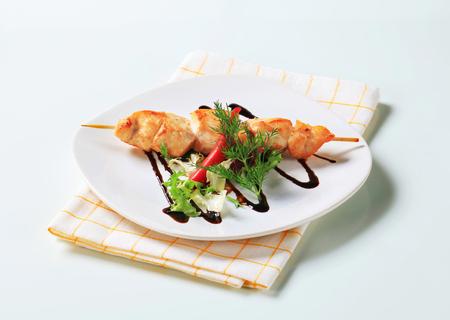 salad greens: Chicken skewer garnished with salad greens and balsamic vinegar