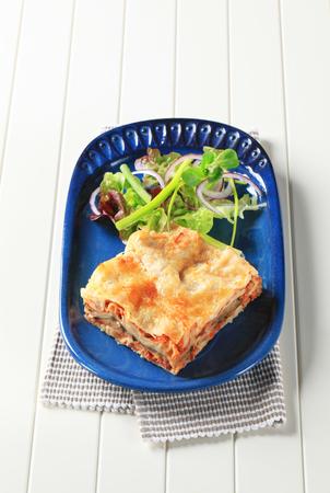 salad greens: Portion of lasagna garnished with salad greens Stock Photo