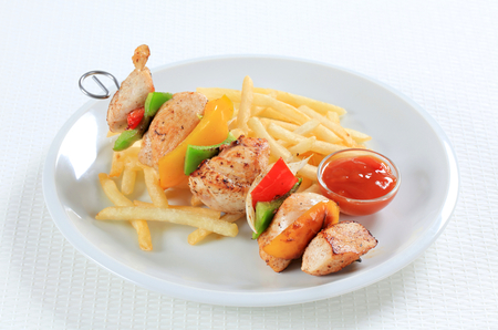 frites: Chicken Shish kebab with French fries and ketchup Stock Photo