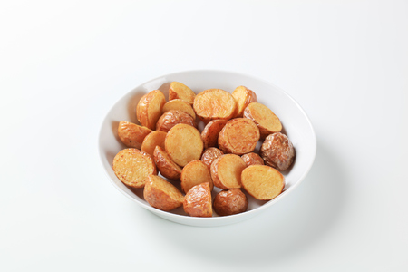 halved  half: Oven-roasted new potatoes in a porcelain dish