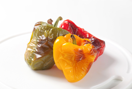accompaniment: Three roasted bell peppers on a cutting board Stock Photo