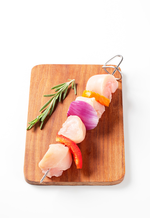 skewer: Raw chicken skewer on cutting board Stock Photo