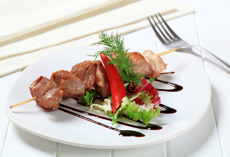 drizzle: Pork skewer garnished with fresh salad and drizzle sauce Stock Photo