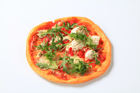 Cheese pizza sprinkled with fresh arugula photo