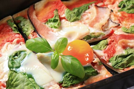 sunny side: Pizza with prosciutto, spinach leaves and sunny side up egg on top