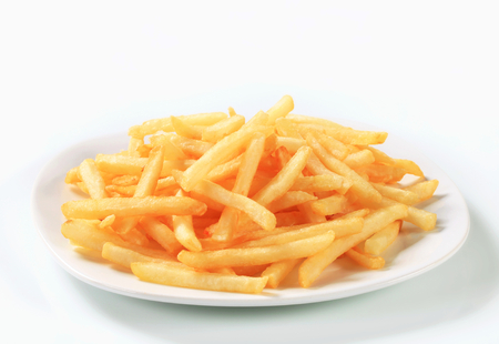 Fresh fried French fries on plate Imagens
