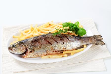 plato de pescado: Plato de la trucha a la parrilla y papas a la francesa Foto de archivo