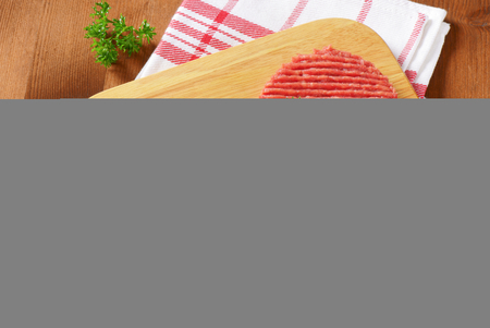 dishtowel: two raw hamburger patties with parsley on wooden cutting board and checkered dishtowel