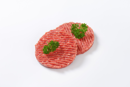 mincing: two raw hamburger patties with parsley on white background