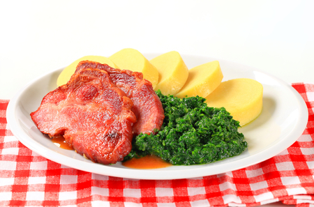 high calorie foods: Pan roasted smoked pork neck with potato dumplings and spinach Stock Photo